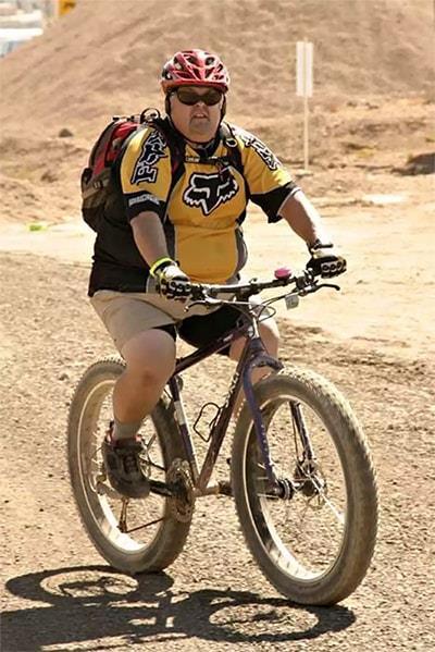 Крупный велосипедист на велосипеде со стальной рамой