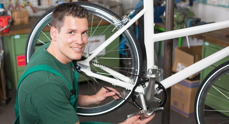 Велосипедный мастер ремонтирует велосипед