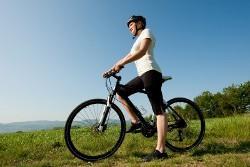 молодая женщина на велосипеде на фоне красивой природы