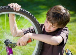 мальчик чинит велосипед