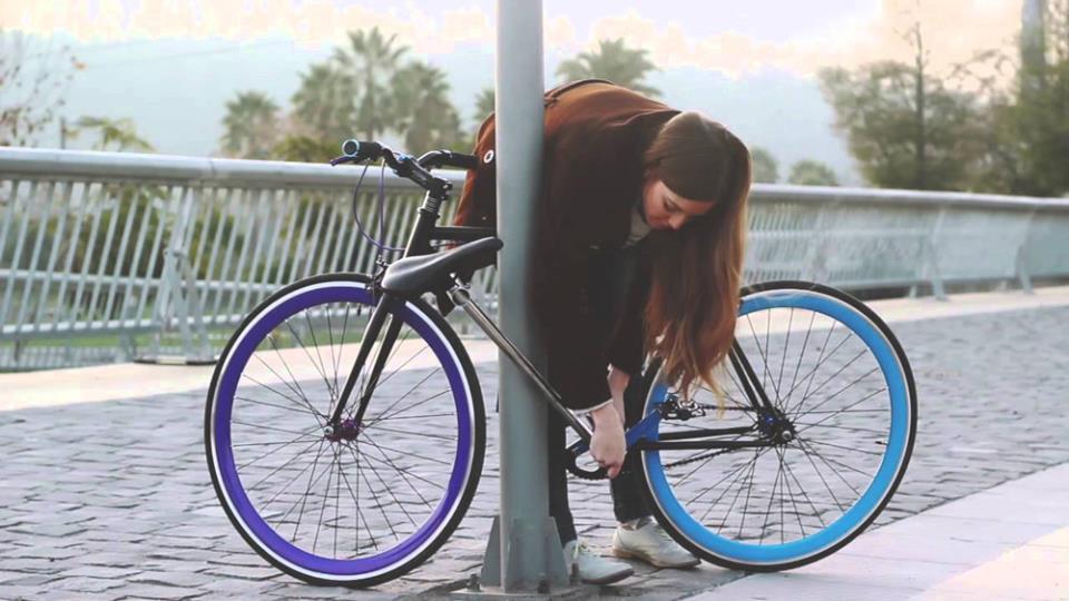 Девушка пристегивает велосипед к столбу