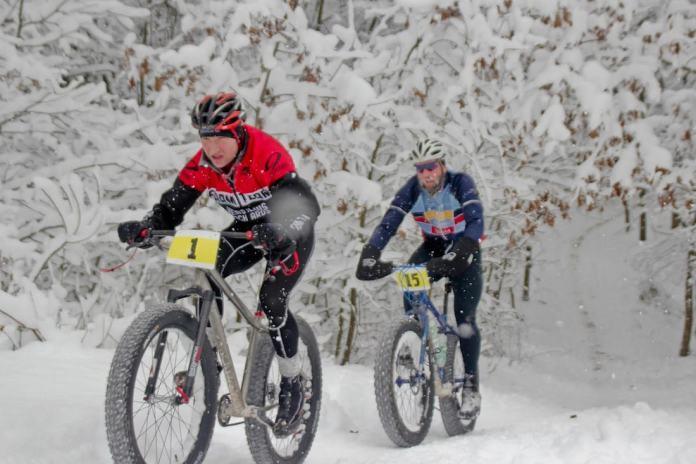 Люди едут по снегу на велосипеде с широкими колесами
