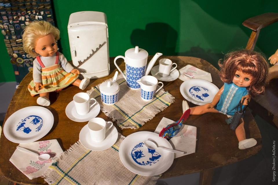 """Детский сервиз и мини-холодильник """"Москвич"""", а также две куклы распивающие выдуманный чай."""