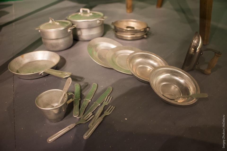 Игрушечные кухонные предметы (тарелки, кастрюли, вилки, ножи) и утюг советского производства.