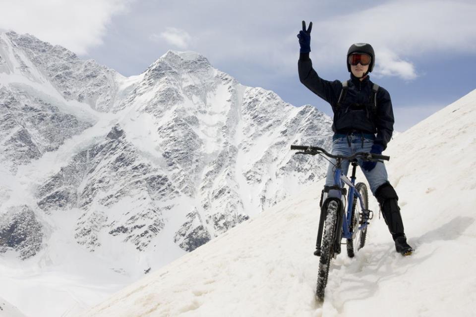 Человек на велосипеде в заснеженных горах